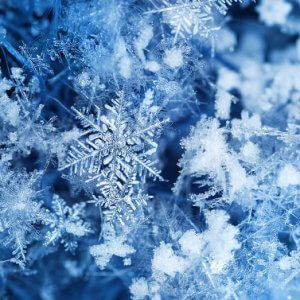 Real ice crystals on blue background after snowfall